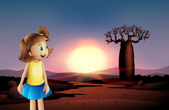 A small girl at the desert wearing a blue skirt Stock Image
