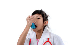 Small girl in doctor's coat inhaling medicine Royalty Free Stock Photography