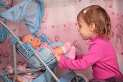 Small girl with doll in carriage Royalty Free Stock Photo