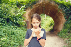 Small girl drawing in notebook near arch bridge. Small teenage girl with smartwatch drawing in notebook near beautiful old arch bridge in park. Cute hispanic Stock Images