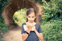 Small girl drawing in notebook near arch bridge. Small teenage girl with smartwatch drawing in notebook near beautiful old arch bridge in park. Cute hispanic Royalty Free Stock Photos