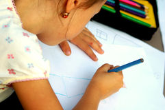 Small girl drawing a picture. Young girl drawing a picture with a crayon Stock Photo