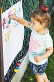 Small girl draws by the brush colorful paintings Royalty Free Stock Image