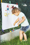 Small girl draws by the brush colorful paintings Royalty Free Stock Photos