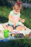 Small girl draws by the brush colorful paintings Royalty Free Stock Photography