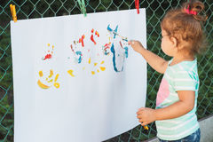 Small girl draws by the brush colorful paintings Stock Image