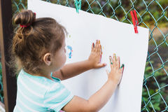 Small girl draws painted hands Stock Photos