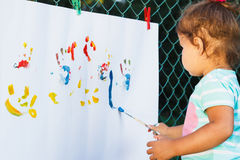 Small girl draws by watercolor Royalty Free Stock Images