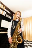 Small girl in dress plays on alto saxophone Royalty Free Stock Photos