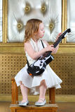 A small girl in dress sitting with guitar Stock Photography