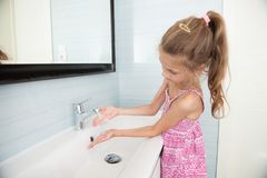 Cute little girl in dress washes her hands in washbasin in bright bathroom royalty free stock photos