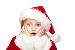 Small girl dressed as santa claus looks surprised Royalty Free Stock Images