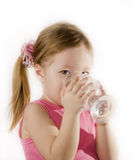 Small girl is drinking the water. From a glass Stock Photos