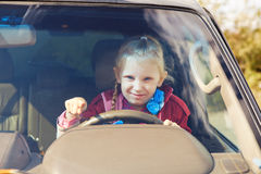 Small girl driving a car Royalty Free Stock Images