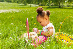 Small girl with Eastern egg and rabbit in park Stock Image
