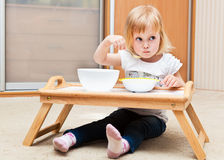 A small girl is eating Stock Photos
