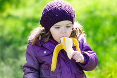 Small girl eating a banana Royalty Free Stock Photos