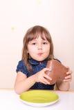 Small girl eating chocolate heart. Little girl eating chocolate heart Royalty Free Stock Images