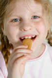 Small girl eating cookie. Small happy blond girl eating a cookie Royalty Free Stock Images