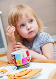 A small girl is eating cookies Stock Photography