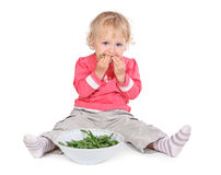 Small girl eating grean peas Royalty Free Stock Photography