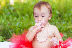Small girl eating her first birthday cake. Small girl funny eating her first birthday cake Stock Image