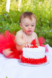 Small girl eating her first birthday cake. In the garden Stock Photos