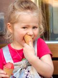 A small girl eating two ice creams. A young blond caucasian girl holding two raspberry ice creams. Eating in front of the ice cream ice cream in a brown cone in stock photos
