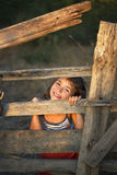 Small girl enjoy being behind an old wooden fence Stock Image