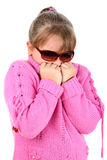 Small girl feeling cold breathing on her hands. Portrait of pre-teen blonde girl in pink sweater isolated on white background Royalty Free Stock Photography