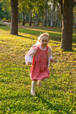 Small girl fun runs in a park Royalty Free Stock Image