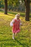 Small girl fun runs in a park. Small girl fun runs in the park Royalty Free Stock Image