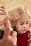 Small girl getting hair done. Stock Image