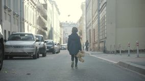 Small girl goes with her teddy bear along a city lane in autumn in slo-mo stock footage