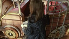 Small girl goes to a carousel and takes a seat in a park in autumn in slow motion stock video footage