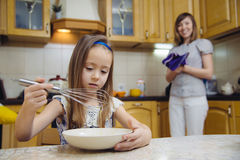 Small girl going to beat the dough for pancakes. Little  mothers helper. Small girl going to beat the dough for pancakes Stock Photo