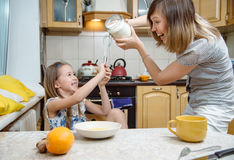Small girl going to beat the dough for pancakes. Little  mothers helper. Small girl going to beat the dough for pancakes Stock Photography