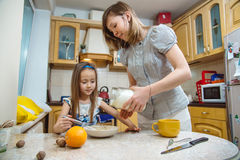 Small girl going to beat the dough for pancakes. Little  mothers helper. Small girl going to beat the dough for pancakes Stock Image