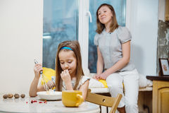 Small girl going to beat the dough for pancakes. Little  mothers helper. Small girl going to beat the dough for pancakes Royalty Free Stock Photo