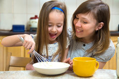 Small girl going to beat the dough for pancakes Royalty Free Stock Photos