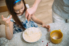 Small girl going to beat the dough for pancakes. Little  mothers helper. Small girl going to beat the dough for pancakes Stock Images