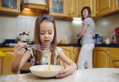 Small girl going to beat the dough for pancakes. Little  mothers helper. Small girl going to beat the dough for pancakes. Mom teach daughter to cook Royalty Free Stock Photography