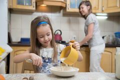 Small girl going to beat the dough for pancakes. Little  mothers helper. Small girl going to beat the dough for pancakes. Mom teach daughter to cook Stock Photos