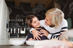A small girl with grandmother cooking at home. A small girl with her grandmother at home, cooking. Family and generations concept Royalty Free Stock Photos