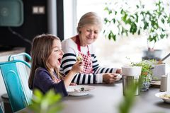 A small girl with grandmother at home. A small girl with grandmother at home, eating. Family and generations concept Stock Images