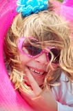 Smiling face on a little girl hair blowing and pink sunglasses. Stock Image