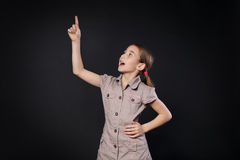 Small girl has idea. Child shows finger up, eureka sign Stock Image