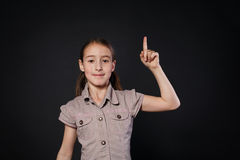 Small girl has idea. Child shows finger up, eureka sign Royalty Free Stock Photo