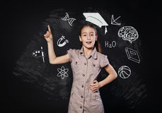 Small girl has idea near chalkboard. Child shows finger up Royalty Free Stock Photo