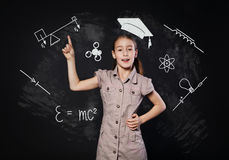 Small girl has idea near chalkboard. Child shows finger up Royalty Free Stock Image